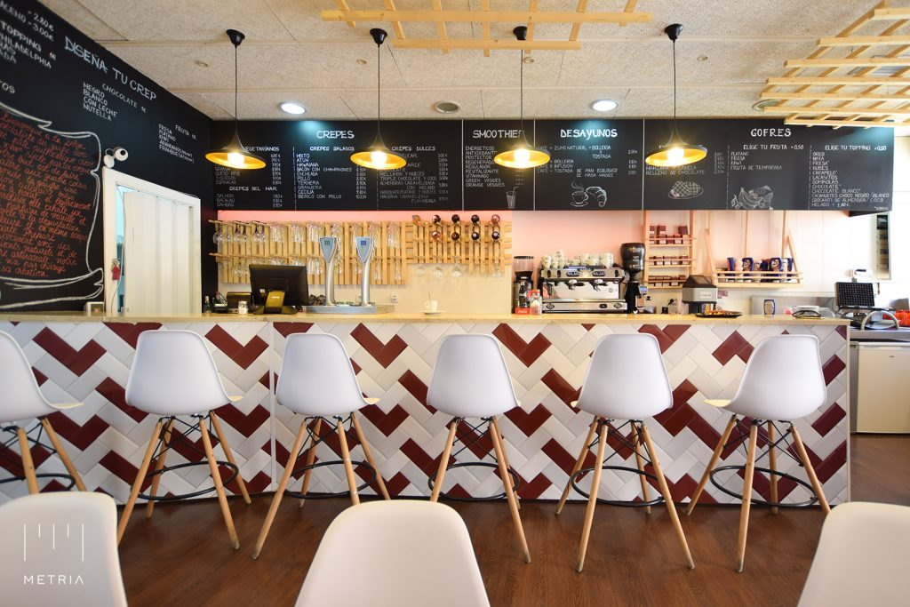 Barra de bar con mosaico de azulejos tipo Metro, pizarras con carta, gofres en techo